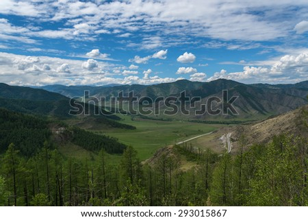 Scenic top view on the valley between the mountains, road, hills covered with vegetation, forest, blue sky and clouds - stock photo