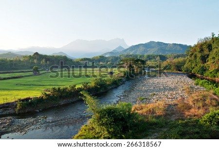 Scenic tropical landscape of Togudon Valley, Kota Belud, Sabah, Malaysia with Mount  Kinabalu as background- image is blurry and for background purposes only. - stock photo
