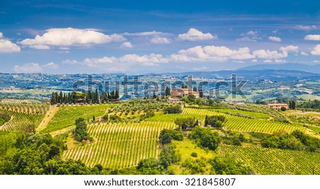 Scenic Tuscany landscape with rolling hills and valleys on a sunny day with blue sky and clouds in Val d'Orcia, Italy - stock photo