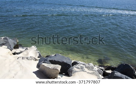 Scenic view from  the rocky fishing groyne in  Leschenault Estuary  at the Cut near Australind , South Western Australia on a fine sunny morning in late summer is calm and peaceful. - stock photo