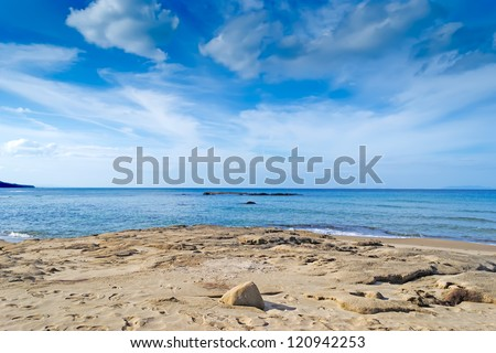 scenic view of a beach with sand under a cloudy sky - stock photo