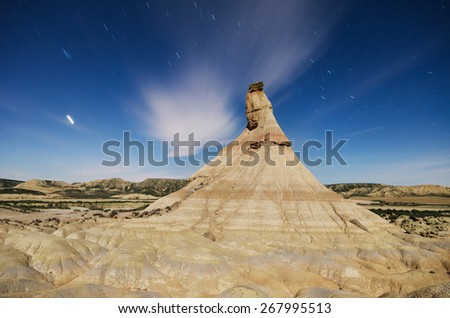 Scenic view of a desertic landscape at night with star trails in Bardenas reales, Navarra, Spain. - stock photo