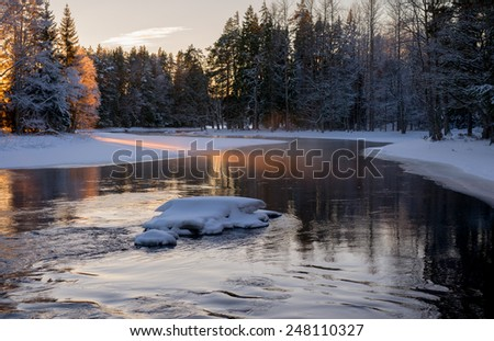 Scenic view of a flowing river in winter  - stock photo