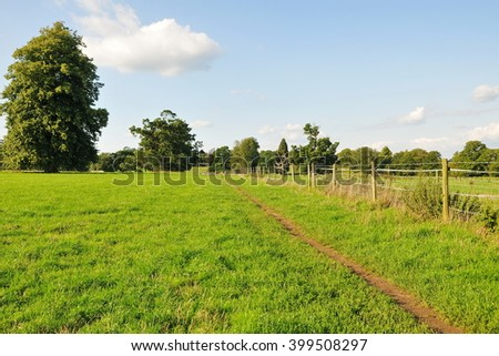 Scenic View of a Footpath through a Green Field  - stock photo