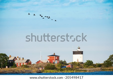 Scenic view of a lighthouse in sweden with a group of Coromants flying by in formation, Svartklubben - Sweden - stock photo