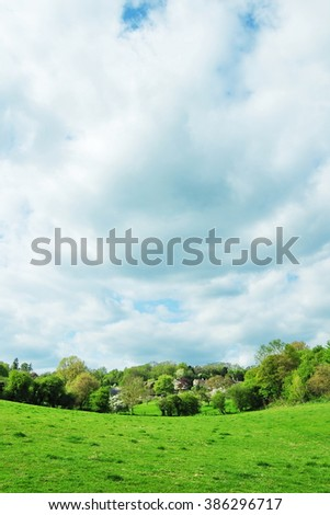 Scenic View of a Lush Green Valley Field with a Stormy Sky Above - stock photo