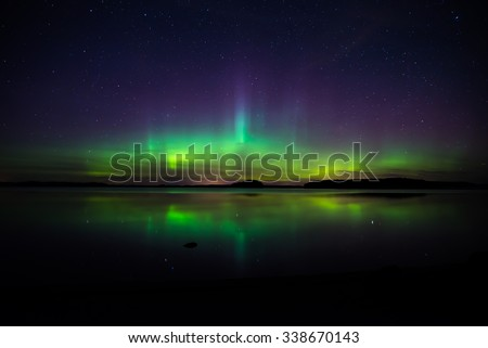 Scenic view of a northern lights over calm lake in Sweden (Aurora borealis) - stock photo