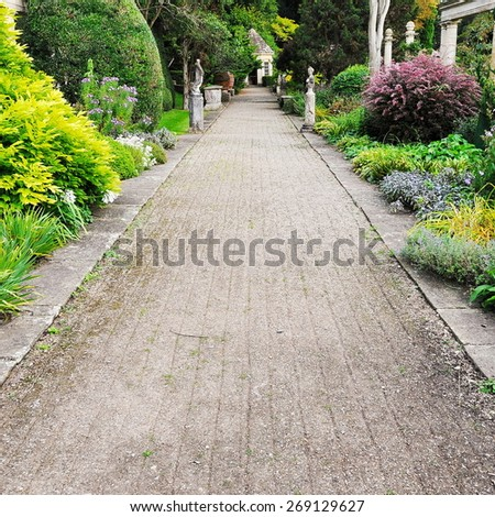 Scenic View of a Pebble Path through a Beautiful Landscape Garden - stock photo