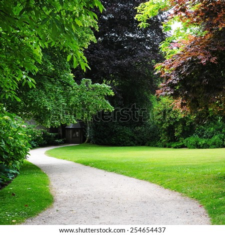 Scenic View of a Winding Path through a Peaceful Woodland Garden - stock photo