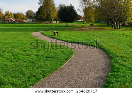 Scenic View of a Winding Stone Path through a Peaceful Green City Park - stock photo