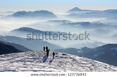 Scenic view of Fagaras Mountains in winter with peaks and foggy valleys - stock photo