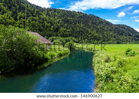 Scenic view of forested Alpine landscape in summer with river in foreground, Switzerland. - stock photo