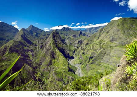 Scenic view of green mountains in Reunion Island National Park with blue sky and cloudscape background. - stock photo