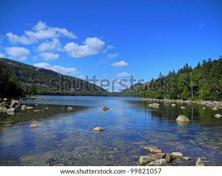 Scenic view of Jordan Pond in Acadia National Park in Maine, with reflections of the blue sky, clouds, and rocks, in the water. - stock photo