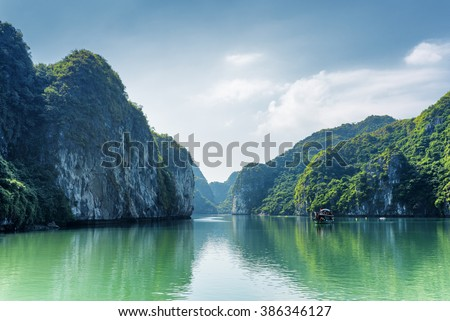 Scenic view of lagoon in the Halong Bay (Descending Dragon Bay) at the Gulf of Tonkin of the South China Sea, Vietnam. Beautiful landscape formed by karst towers-isles on blue sky background. - stock photo