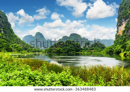 Scenic view of lake among karst towers at Ninh Binh Province, Vietnam. Blue sky with clouds is visible in background. Ninh Binh Province is a popular tourist destination of Asia. - stock photo