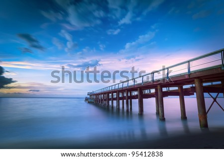 Scenic view of long wooden pier on shoreline with colorful sunset and cloudscape background, Reunion Island. - stock photo