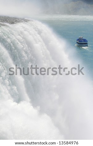 Scenic view of Niagara falls with boat full of tourists going to see the Horseshoe Bend falls - stock photo