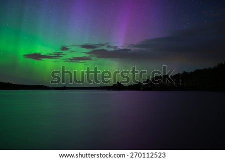 Scenic view of northern lights over lake (Aurora borealis) - stock photo