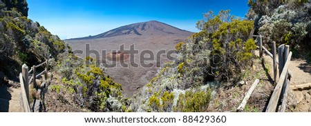Scenic view of Piton de la Fournaise volcano viewed from the caldera with a track in foreground, Reunion Island National Park. - stock photo