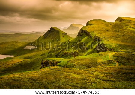 Scenic view of Quiraing mountains sunset with dramatic sky in Scottish highlands, Isle of Skye, United Kingdom - stock photo