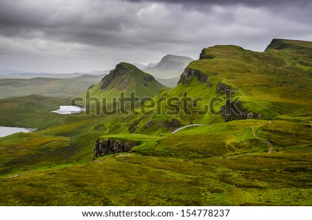 Scenic view of Quiraing mountains with dramatic sky in Scottish highlands, Isle of Skye, United Kingdom - stock photo