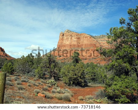 Scenic view of Sedona brush, trees, and mesa with red rock columns. - stock photo