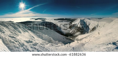 Scenic view of sun shining over snow covered Giant mountains, Czech Republic. - stock photo