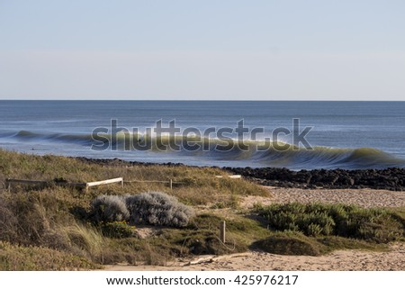 Scenic view of  the  Indian Ocean waves breaking onto the sandy shore  at  Ocean Beach Bunbury Western Australia on a fine  morning in winter  is fascinating to watch. - stock photo