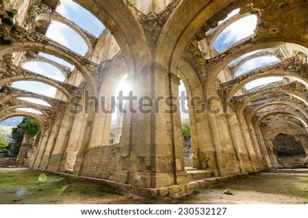 Scenic view of the ruined cloister of an abandoned monastery. HDR picture with ray of light and lens flare effect. - stock photo