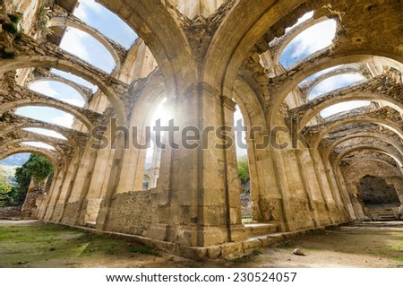 Scenic view of the ruined cloister of an abandoned monastery. HDR picture with ray of light effect. - stock photo