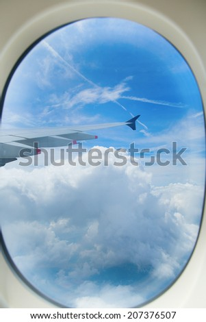 Scenic view through a porthole of an aircraft - stock photo