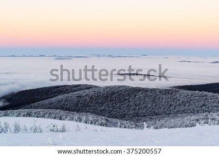Scenic winter landscape above the clouds. The sky is clear. After dusk. Some mountains are seen on the horizon. - stock photo