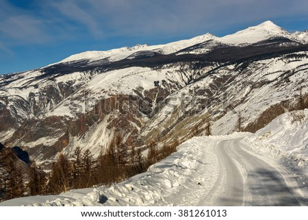 Scenic winter landscape with a winding snowy road in the mountains, mountains covered with snow and the valley between the mountains on the background of blue sky and clouds - stock photo