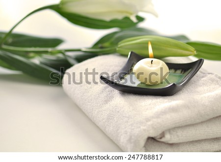 Scented candle and flowers placed on white towel - spa objects - stock photo
