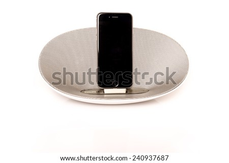 SCHARNHAUSEN, GERMANY - DECEMBER 29,2014: Front view of an Apple iPhone 6 in a Philips docking station and speaker on a white background on December 29, 2014 in Scharnhausen, Germany. - stock photo