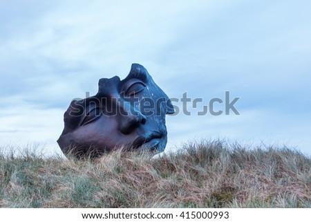 Scheveningen, Netherlands - April 21, 2016: sculpture of Igor Mitoraj in the dunes of Scheveningen. Mitoraj is a famous sculptor. His works are distributed in several European cities - stock photo