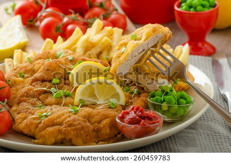 Schnitzel, french fries, cherry tomatoes and fresh microgreens pea salad - stock photo