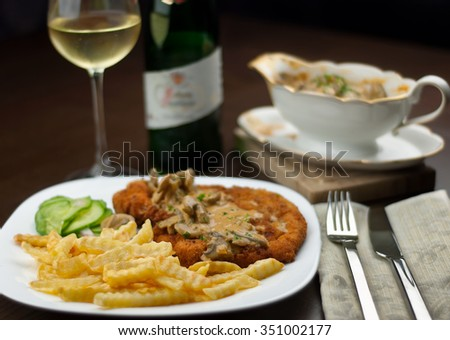 Schnitzel, french fries, cucumber salad and white wine with jaeger or hunter sauce - stock photo