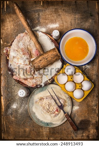 Schnitzel making, preparation composing with ingredients: meat, flour, eggs, crumbs on wooden background, top view - stock photo