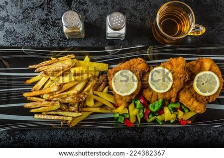 Schnitzel with french fries, homemade, platter, czech beer, vegetable, lemons - stock photo