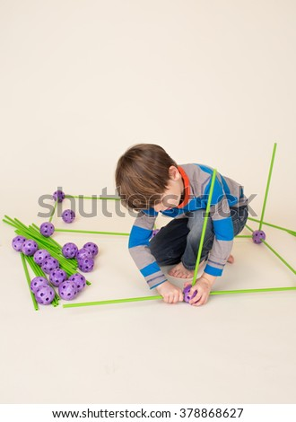 School aged child Building and Playing with Construction Set Pieces - stock photo