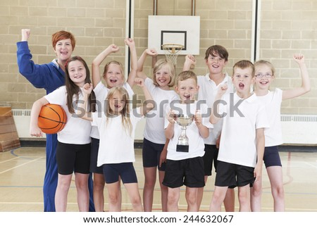 School Basketball Team And Coach Celebrating Victory With Trophy - stock photo