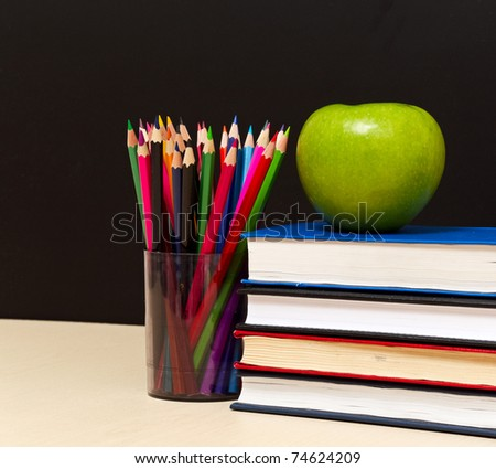 School books with apple on desk, on black school board background - stock photo