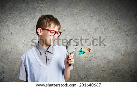 School boy examining butterfly with magnifying glass - stock photo