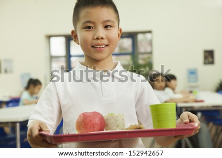 School boy holding food tray in school cafeteria - stock photo