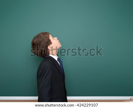 school boy in black suit look up on green chalkboard background, education concept - stock photo