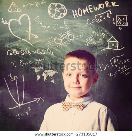 school boy is standing with blackboard behind him - stock photo