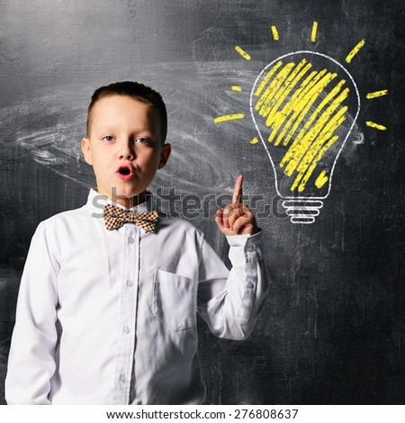 school boy is standing with blackboard behind him - stock photo