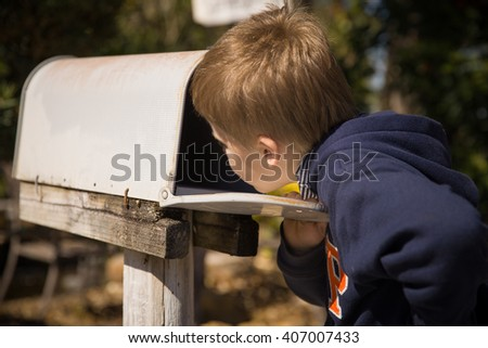 School boy opening a post box and checking mail. Kid waiting for a letter, checking correspondence and looking into the in the metal mailbox. - stock photo